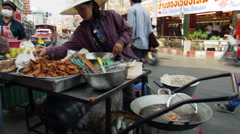 Thailand: Vendor selling fried chicken at a street stall - stock footage