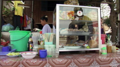 Cambodia: Outdoor food merchant stall, pan to women eating at a nearby table Stock Footage