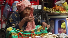 Cambodia: Seated woman eating a meal  near street market stalls Stock Footage