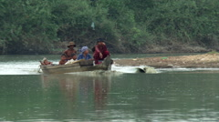 Cambodia: Family riding in a small motorboat along a river - stock footage