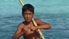 Young Samoan boy biting freshly-caught  fish Stock Footage