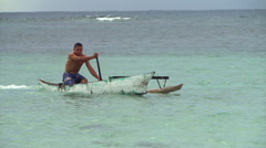 Samoan man paddling an outrigger canoe to shore - stock footage