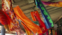 Tilt-down from hanging sarongs to an outdoor market in Samoa - stock footage