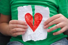 Stock Photo of Child ripping red heart on a piece of paper
