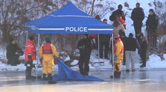 Police officers recover body of missing woman found in pond ice Stock Footage