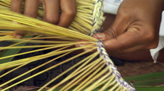 Close-up of Fijian woman's hands as she makes a broom from palm fronds Stock Footage