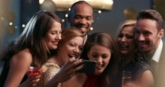 Smiling group of friends celebrate evening event with selfie at party Stock Footage
