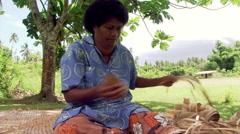 Fijian woman stripping bark and weaving it Stock Footage