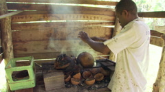 Fijian man roasting fruits over an open fire fueled with coconut hulls Stock Footage