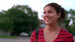 Shoulders-up portrait of a smiling teenage girl near soft-focus school grounds Stock Footage