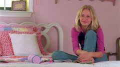 Smiling blond teen sitting on her bed in a pink room Stock Footage