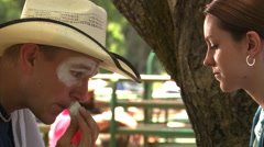 Rodeo clown painting his face before a performance as young woman looks on - stock footage