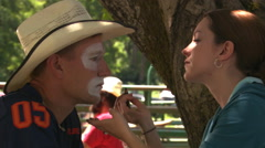 Close view of a rodeo clown's face and a young woman helping him with makeup Stock Footage