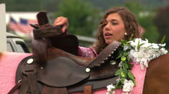 Close view of saddle decorated with flowers and face of young woman preparing to Stock Footage