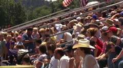 Crowd in bleachers preparing to watch a rodeo Stock Footage