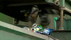 Sorting aluminum cans of beer beverage and out of soft drinks at recycling plant - stock footage