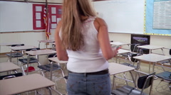 Students coming to class as teacher writes on board, viewed from back of Stock Footage