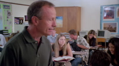Teacher moving through classroom where seated students do an assignment Stock Footage