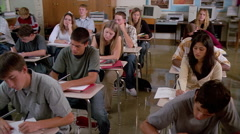 Pan over seated students, many hands going up and students smiling - stock footage