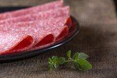 Salami slices on plate - stock photo
