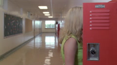 Pregnant teen getting textbooks from locker, walking down long hall as boys pass Stock Footage