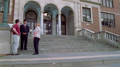 Students leaving high school, two pausing to say good-bye to teachers and - stock footage