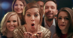 Beautiful woman blowing glitter at glamorous party Stock Footage