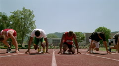 Four runners leaving the starting blocks, viewed at ground level in slow motion Stock Footage