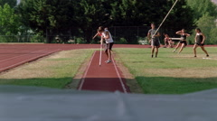 Pole vaulter approaching and jumping to clear the bar, slow motion Stock Footage