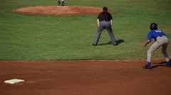 Runner sliding, umpire signals him safe on base, viewed in slow motion from Stock Footage