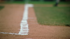 Slow-motion close-up of base runner's cleats rounding third base - stock footage