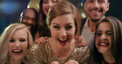 Beautiful woman blowing glitter at glamorous party - stock footage