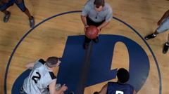 Slow-motion overhead view of basketball players at tipoff Stock Footage