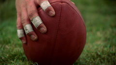 Eye-level close-up of football on turf and hand reaching to tilt it Stock Footage