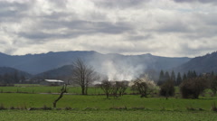 Wide view of rural fields with mountains in background; smoke rising from a Stock Footage