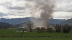 Smoke and flames rising from a burning house across a rural field - stock footage