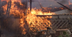 Burning lattice on the side of a house now almost consumed by fire; flaming - stock footage