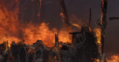 Charred, still blazing remains of a house consumed by fire - stock footage