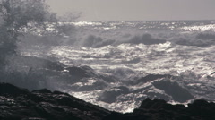 Stormy gray waves advancing toward dark rocks in foreground - stock footage