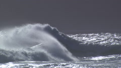 Silver-capped waves cresting and breaking into spray under gray sky Stock Footage