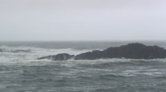 Gray waves breaking on rock in mid-frame and close-up spray near camera - stock footage