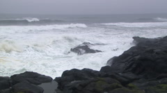 Incoming tide crashing on rocks in foreground under gray skies - stock footage