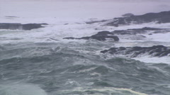 Tossing waves pounding the base of dark seacliffs on a rocky headland - stock footage