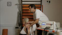 Young male physiotherapist doing massage with massager on shoulder of old woman. Stock Footage