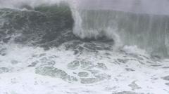 Frame-filling spray-crested wave rolling toward rocks near camera Stock Footage