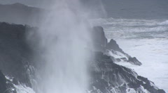 Spray from crashing waves drifting over high rocky outcrops Stock Footage