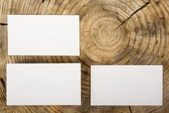Blank white business cards on wood background - stock photo