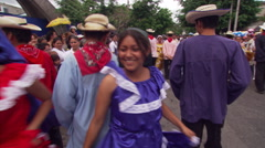 Young folk dancers parading through street in San Salvador, accompanied by band Stock Footage