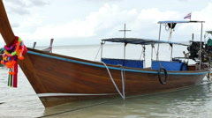 Decorated longtail boats moored at the sandy beach Stock Footage
