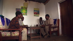 Interior of Tanzanian home, woman serving refreshments to five seated men - stock footage